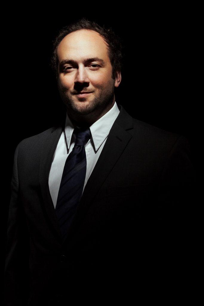 portrait homme veston cravate fond noir éclairage contrasté
