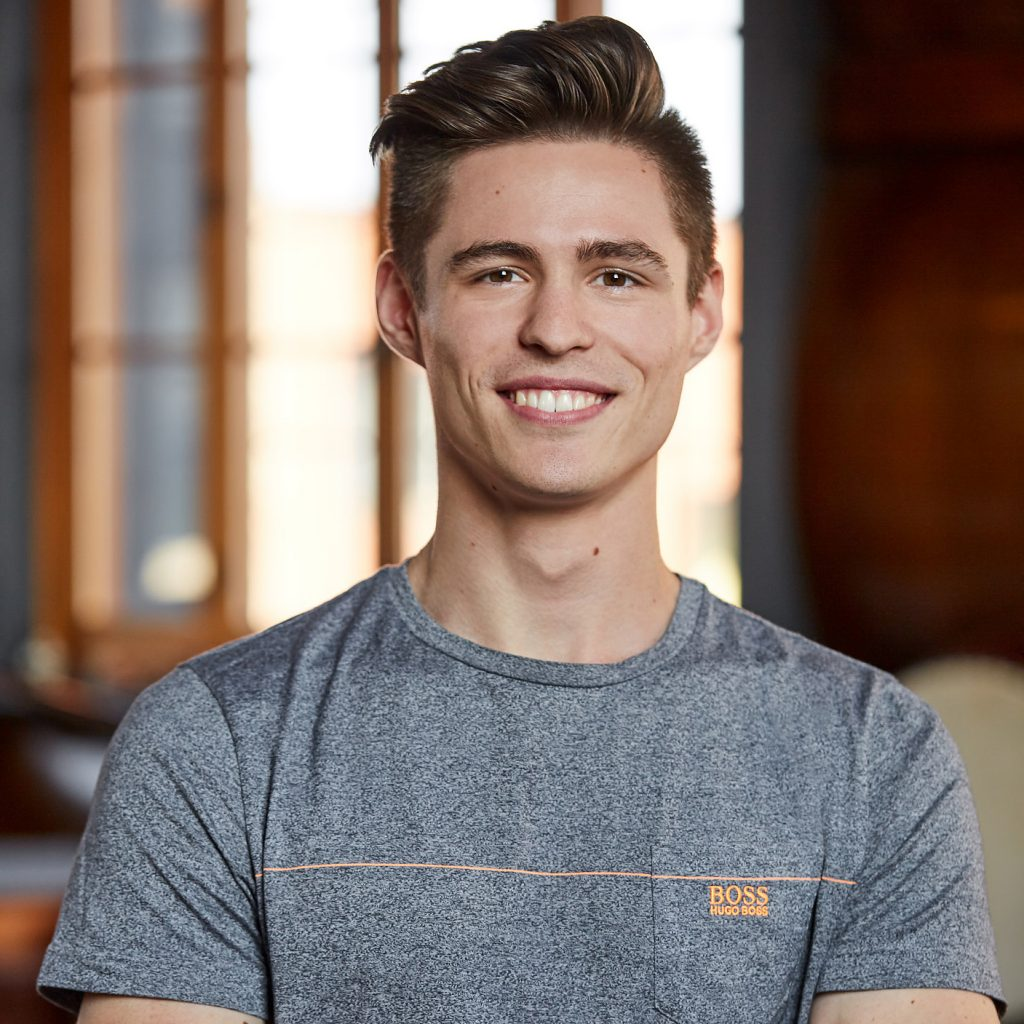 portrait jeune homme souriant chandail gris