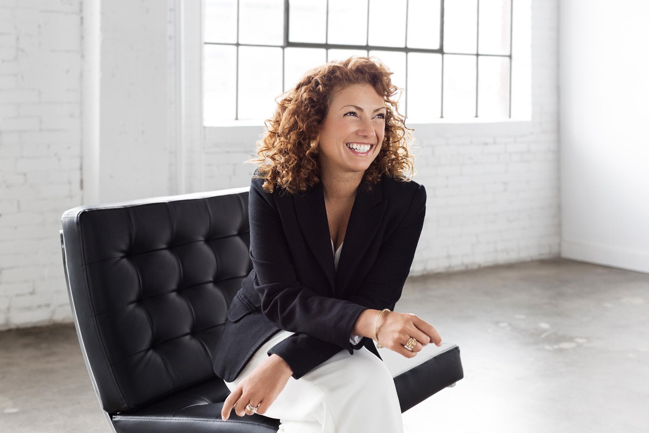 portrait femme assise souriante mur brique blanche