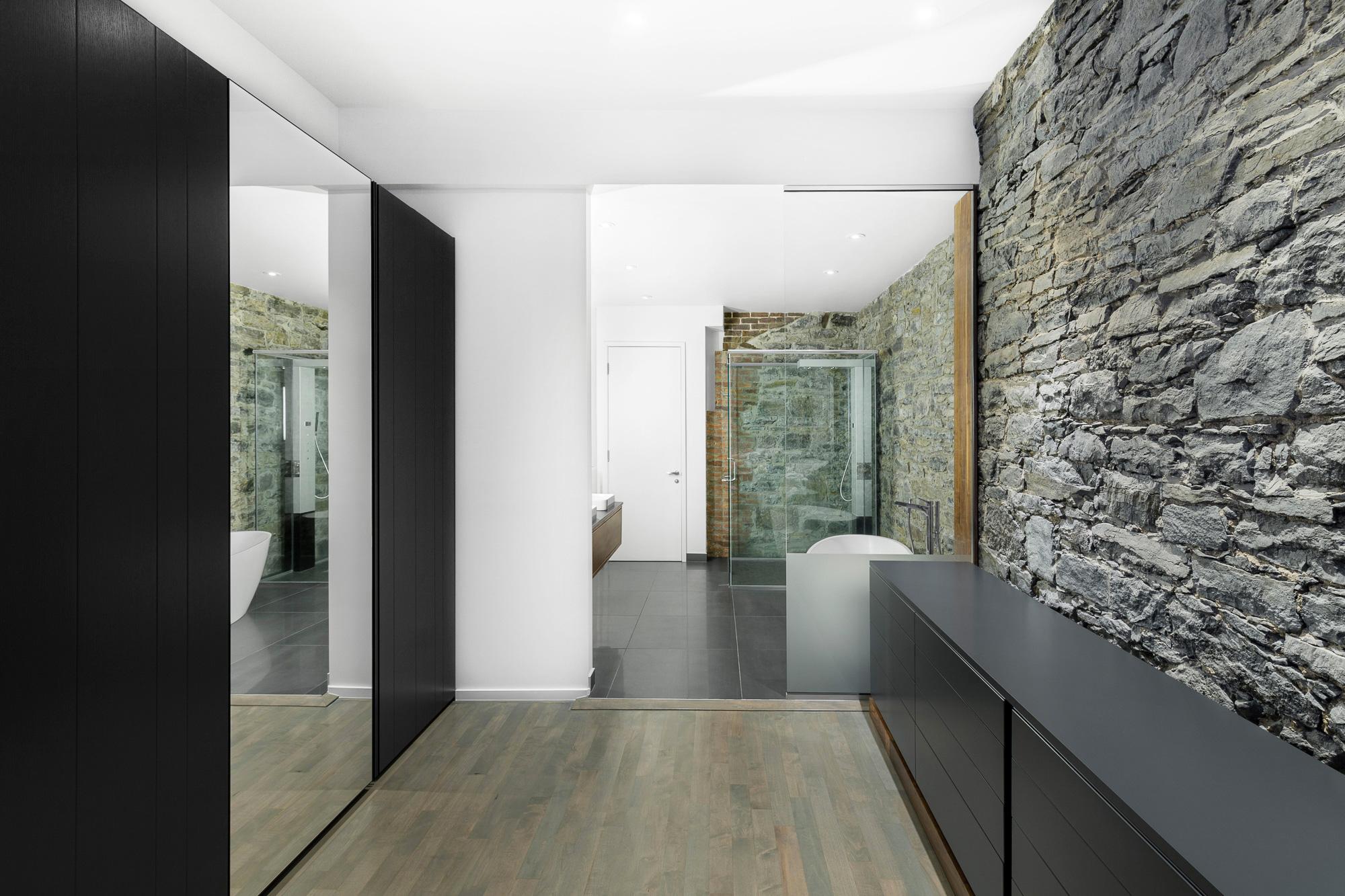 salle de bain meubles noirs mur pierre