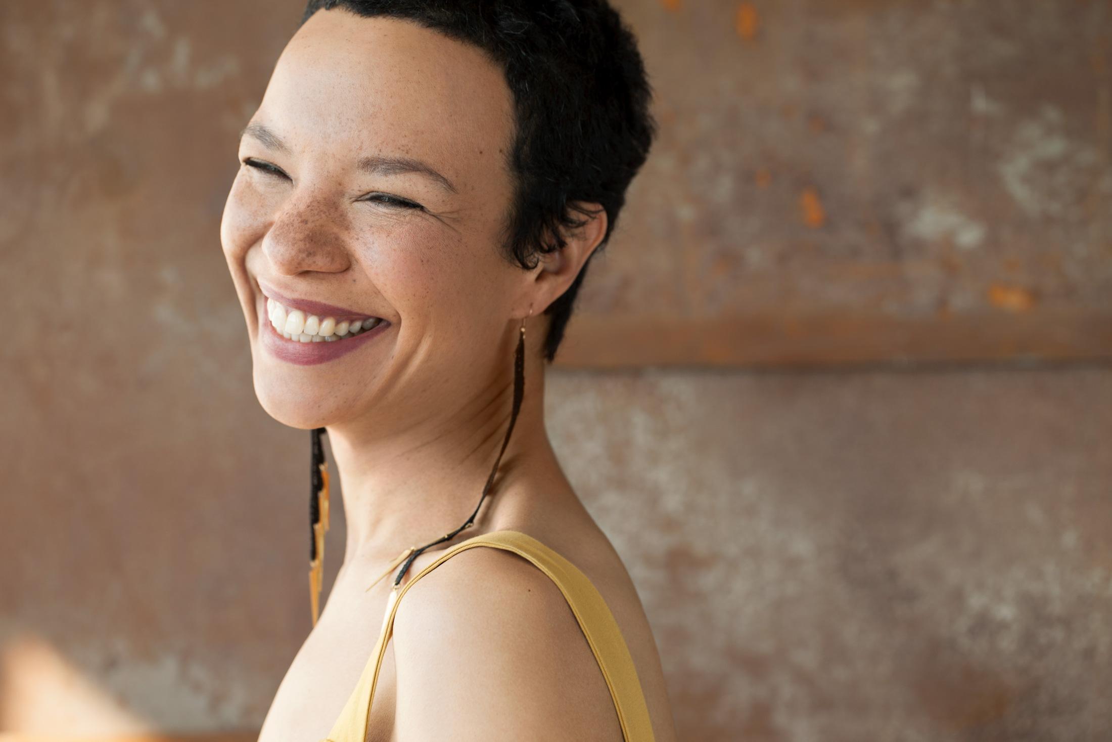 portrait femme grand sourire fond rouillé