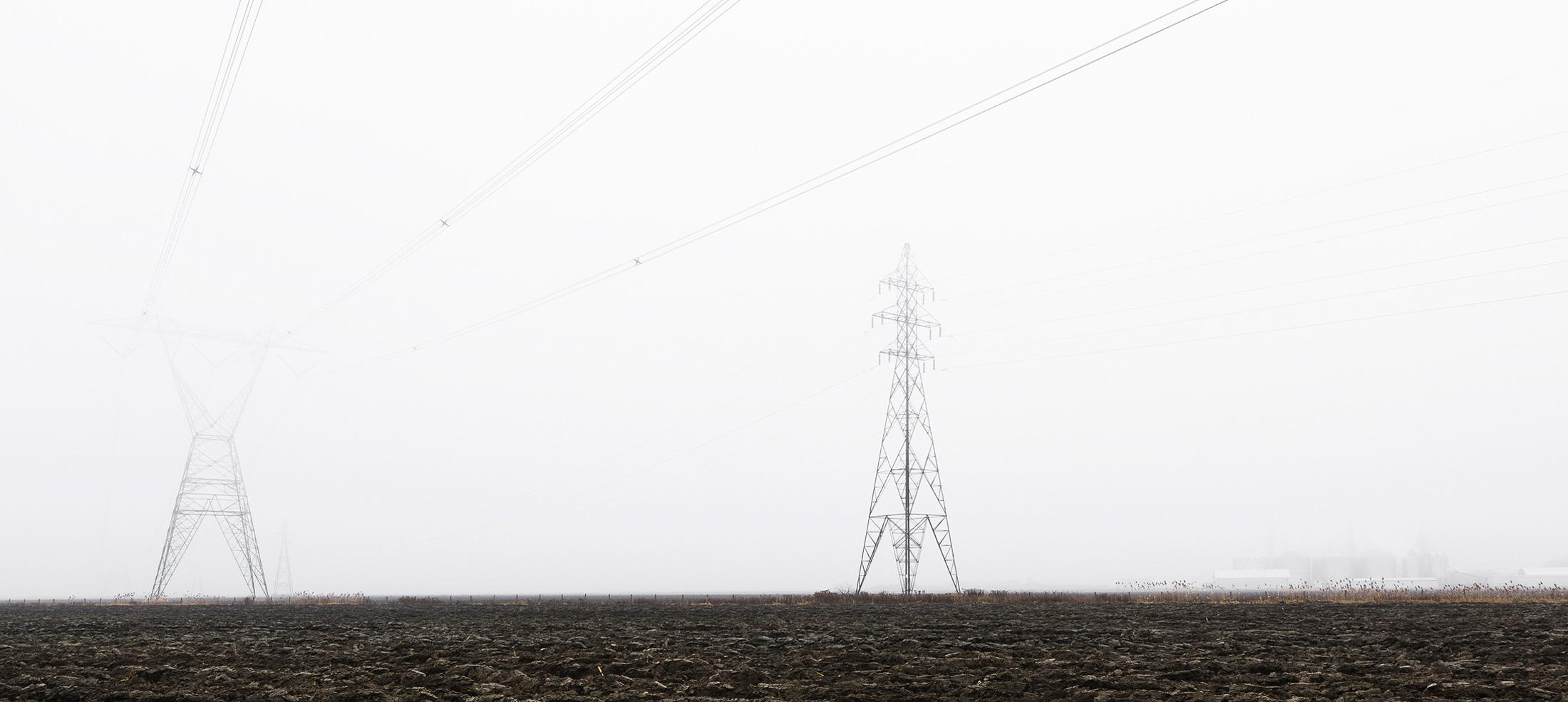 paysage rural champs vides pylônes électriques brume