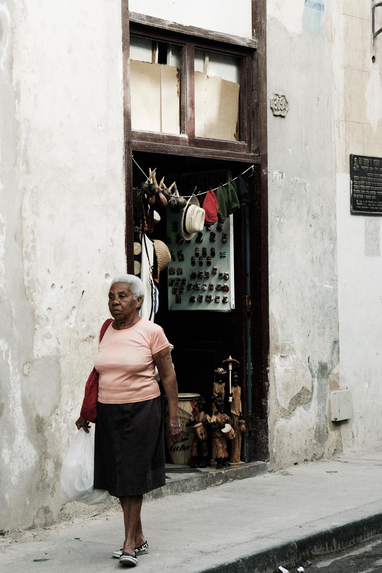 cuba femme marche mur gris porte marchand