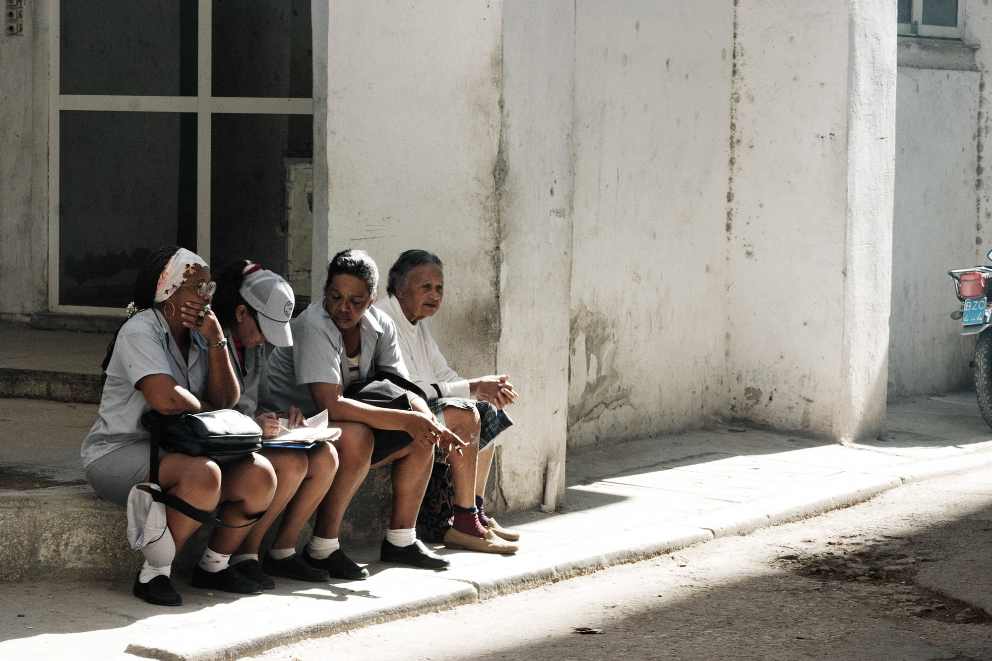 cuba 4 femmes discutent rue murs blancs